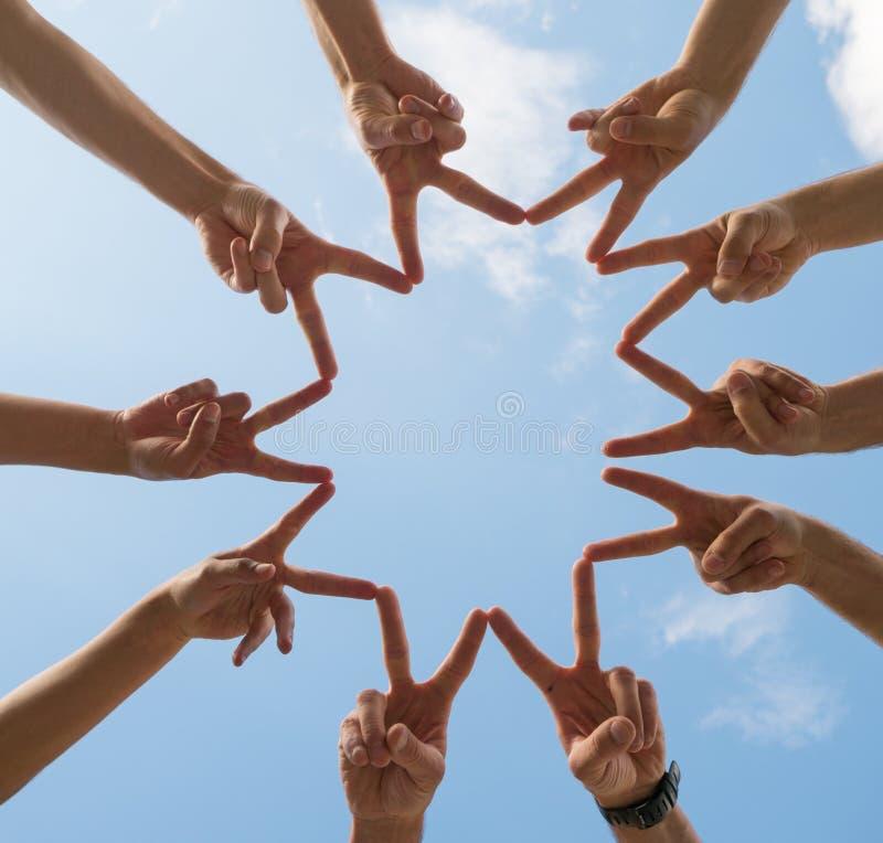 Muitas mãos que fazem sinais de paz sob o céu fotos de stock royalty free