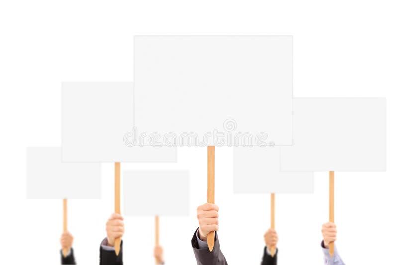 Muitas mãos que guardam bandeiras e sinais vazios foto de stock