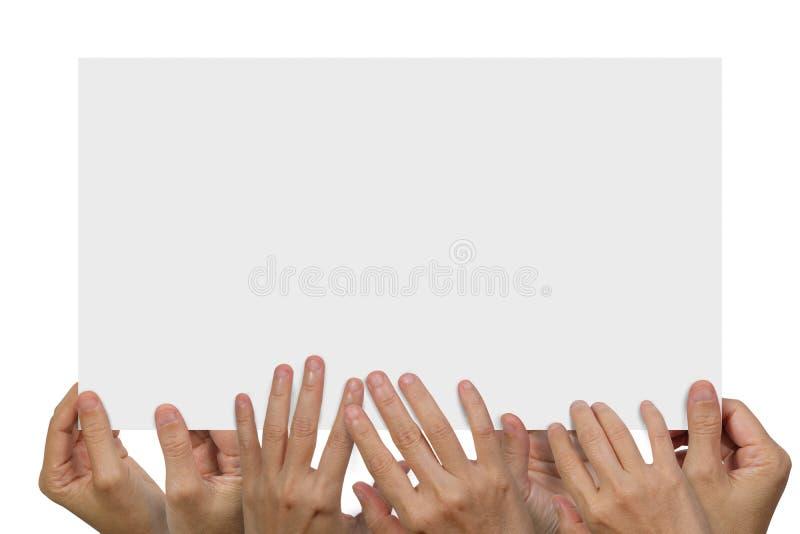 Muitas mãos que guardam um cartaz vazio branco fotografia de stock