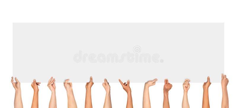 Muitas mãos que guardam um cartaz vazio para anunciar imagem de stock