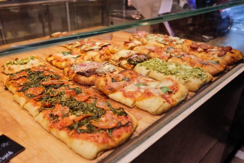 Muitas mini pizzas no contador Tipos diferentes de pizzas em grandes quantidades fotografia de stock royalty free