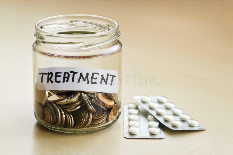 Muitas moedas e palavra do tratamento em um frasco de vidro perto de duas bolhas com comprimidos em uma tabela Dinheiro de salvam fotografia de stock royalty free