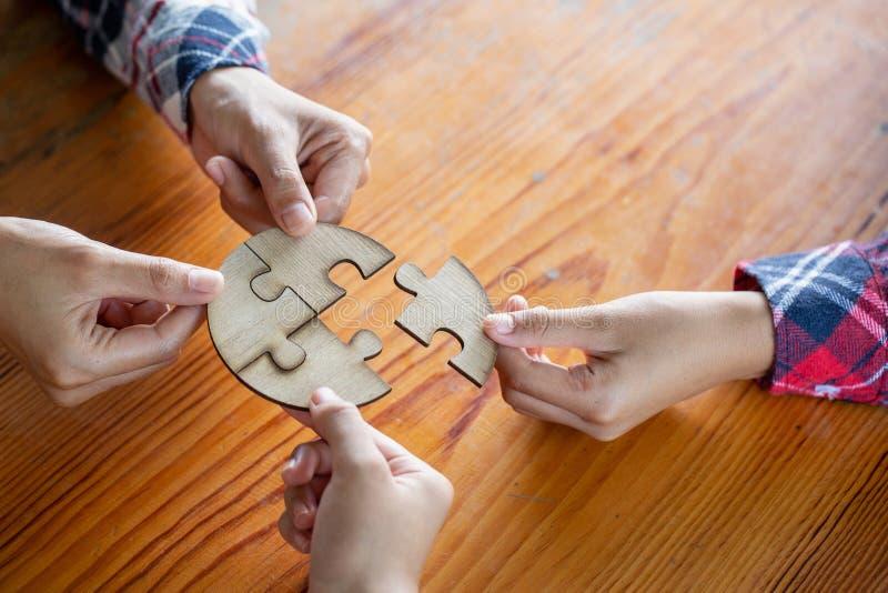 Muitas pessoas que guardam partes de enigma de serra de vaivém, conceito dos trabalhos de equipe, conexão de negócio foto de stock