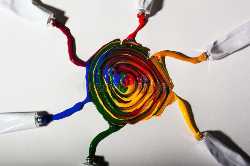 Muitas pinturas coloridos fluem dos tubos misturados no papel e formam o teste padrão do sol africano fotos de stock