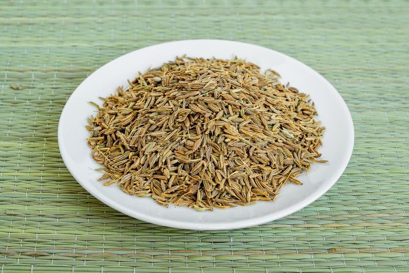 Muitas sementes da alcaravia ou de cominhos em uns pires brancos em uma esteira de tabela verde feita de fibras de planta naturai imagem de stock