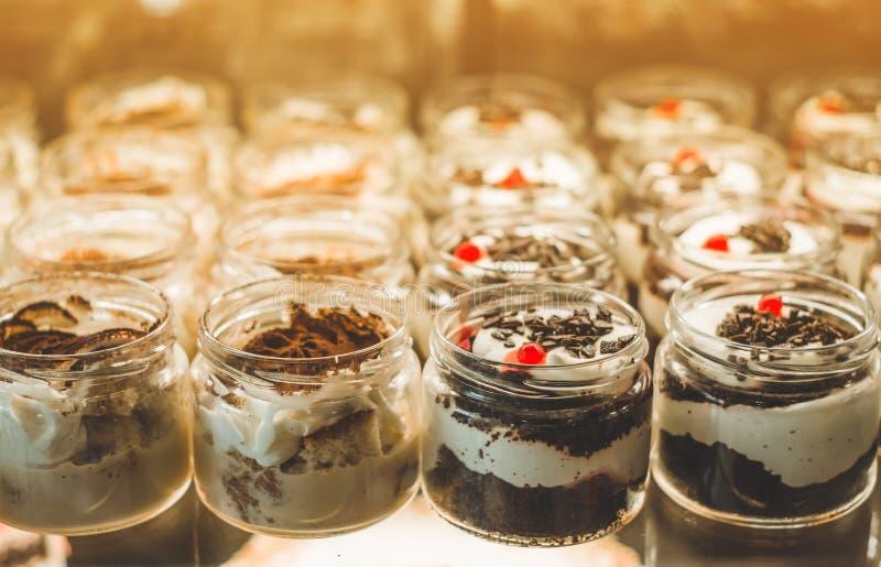 Muitas sobremesas deliciosas em um frasco na janela de um caf? acolhedor Doces saborosos imagens de stock royalty free