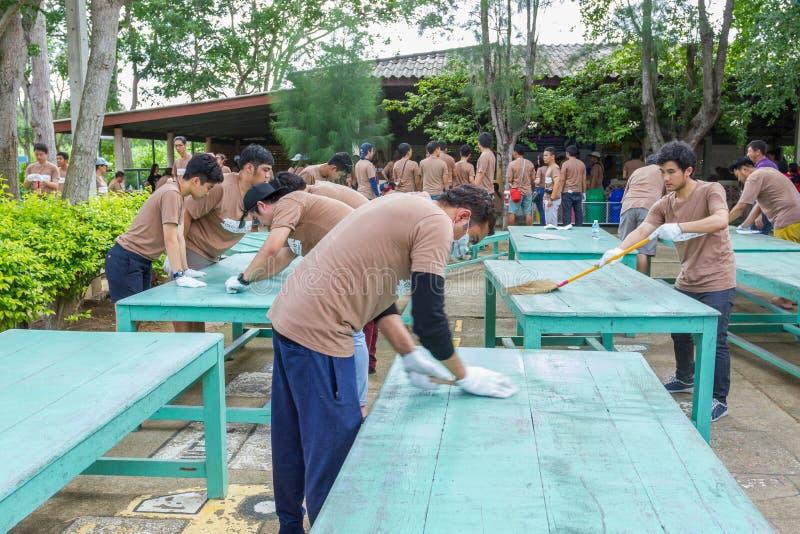 Muitas tabelas de madeira e cadeiras da limpeza ridiculamente dura dos povos antes de pintar foto de stock royalty free