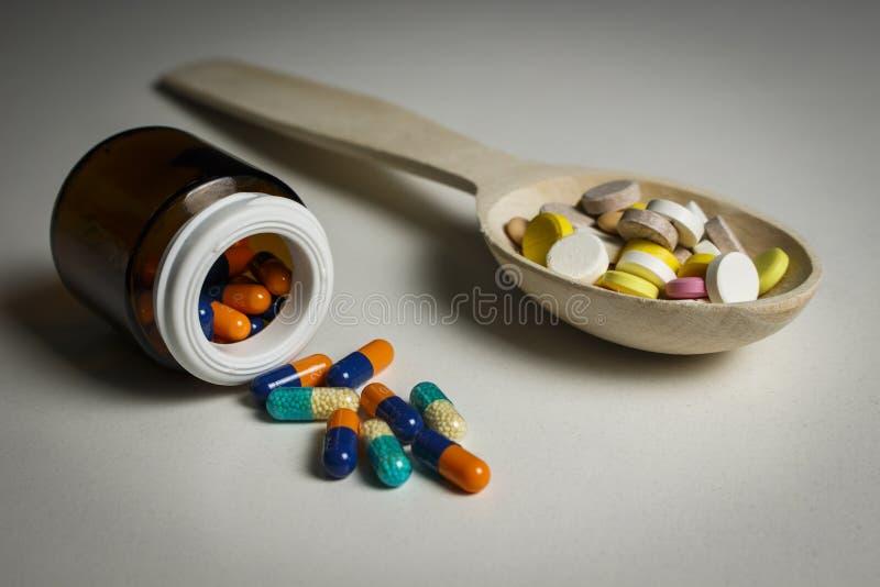 Muitas tabuletas coloridas em uma colher de madeira e em um frasco das cápsulas fotografia de stock