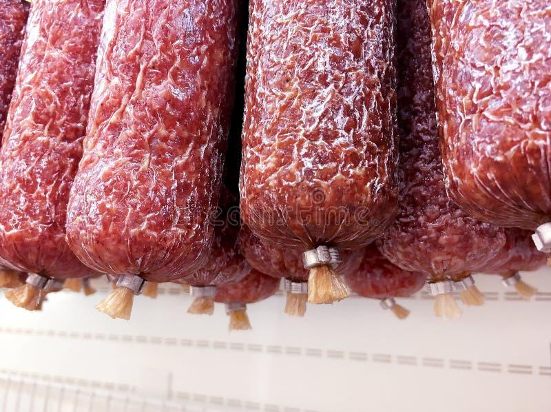 Muitas varas da salsicha fumado que penduram na loja na exposição fotos de stock