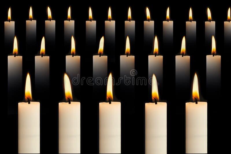 Muitas velas acesas em filas sobre fundo preto. Conceito de fé, religião, honra ou espiritualidade fotografia de stock