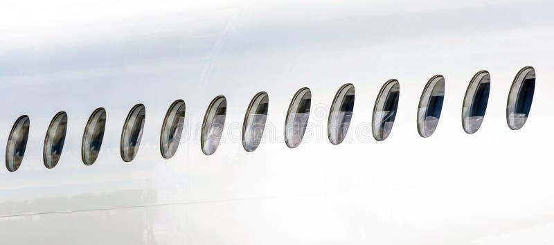 Muitas vigias em seguido na fuselagem de um avião branco imagem de stock