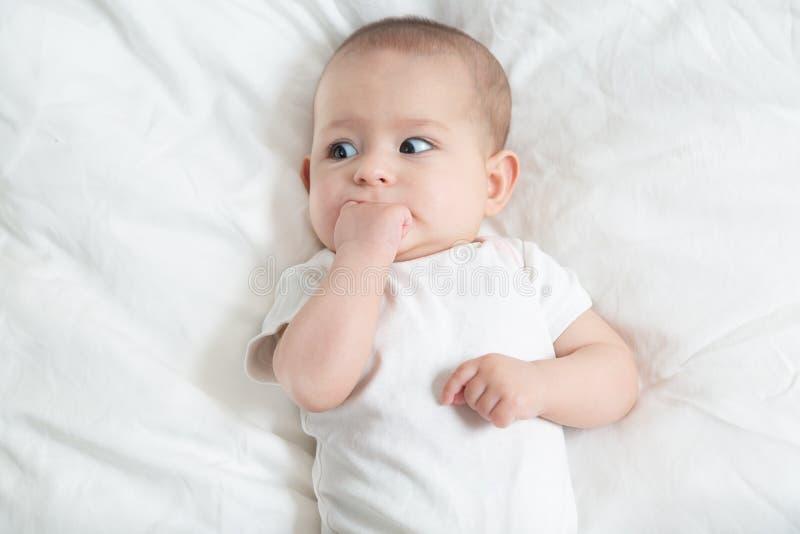 Muito assustado pouco bebê no branco que encontra-se em uma cama branca Sair os dentes do beb? imagem de stock