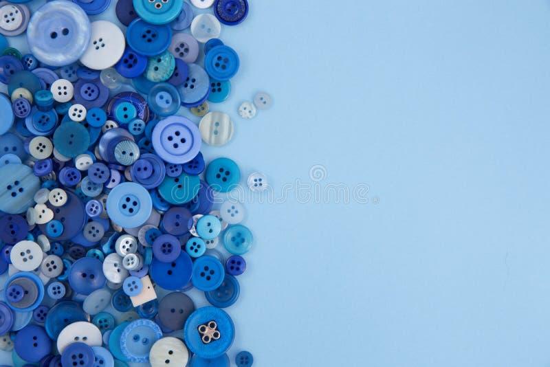 Muito azul abotoa-se para a roupa em uma luz - fundo azul fotos de stock