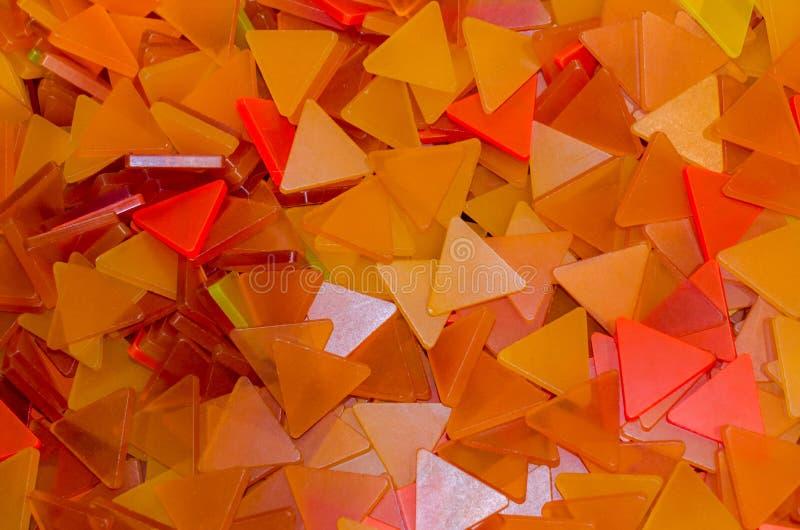 Muito fundo plástico alaranjado dos triângulos Triângulos alaranjados e amarelos foto de stock royalty free