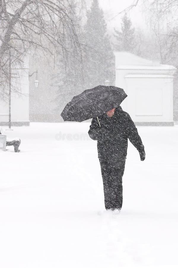 Muito mau tempo em uma cidade no inverno: queda de neve pesada e blizzard Esconder pedestre masculino da neve sob o guarda-chuva, imagens de stock royalty free