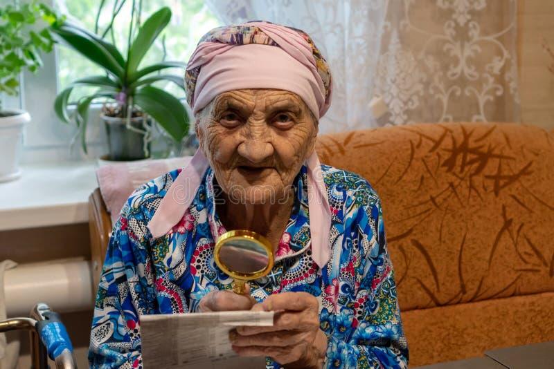 Muito mulher adulta com a lente de aumento que tenta ler de um jornal a avó 90 anos velha lê na tabela com lente de aumento A fotos de stock