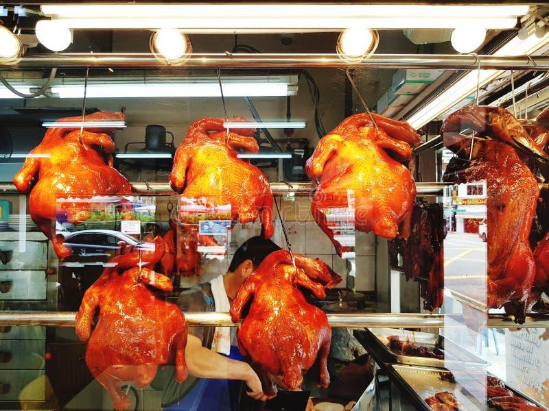 Muito o pato ou a galinha deliciosa roasted o cair no gancho inoxidável para mostrar o alimento da compra do cliente para comer o imagem de stock royalty free