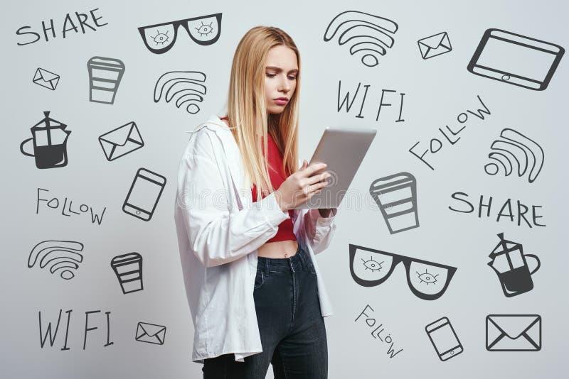 Muito ocupado A menina loura séria em um vestuário desportivo está usando sua tabuleta digital para o estudo ao estar contra o ci imagem de stock