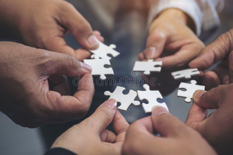 Muito pessoa entrega manter um enigma de serra de vaivém no círculo unido foto de stock