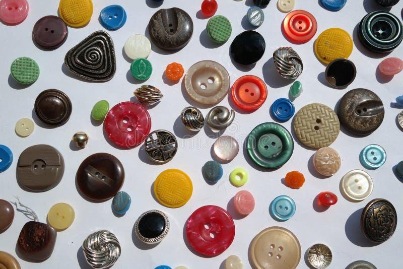 Muito variedade colorida brilhante de botões redondos, texturas diferentes, diâmetro, em um fundo branco imagem de stock