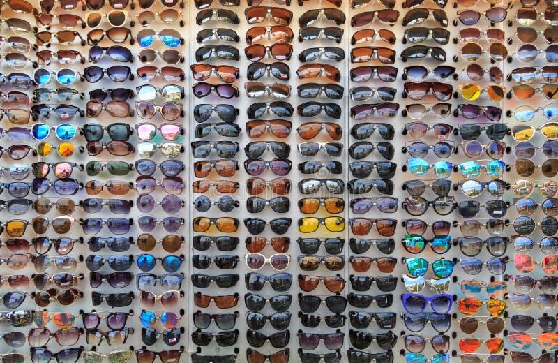 Muitos óculos de sol diferentes estão na montra como um fundo ou um contexto imagem de stock