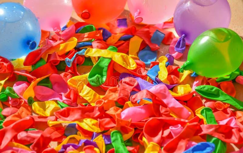 muitos balões coloridos nas telhas de um terraço Alguns balões são desinflados e outros balões estão completos da água e do ar a foto de stock royalty free
