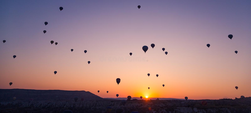 Muitos balões enormes estão voando no ar no nascer do sol Cappadocia, Turquia imagens de stock