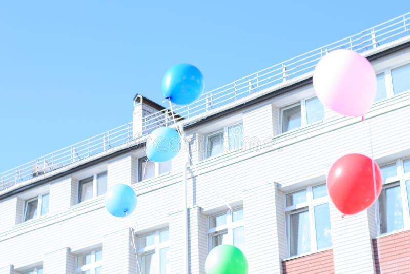 Muitos balões voam no céu claro azul, construindo nos vagabundos imagem de stock royalty free