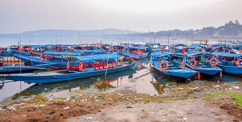 Muitos barcos estacionados na beira do lago imagem de stock