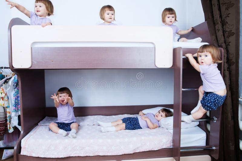 Muitos bebês do clone na cama da barreira na sala de criança na vida doméstica multidão idêntica da criança Criança com emoção di imagens de stock