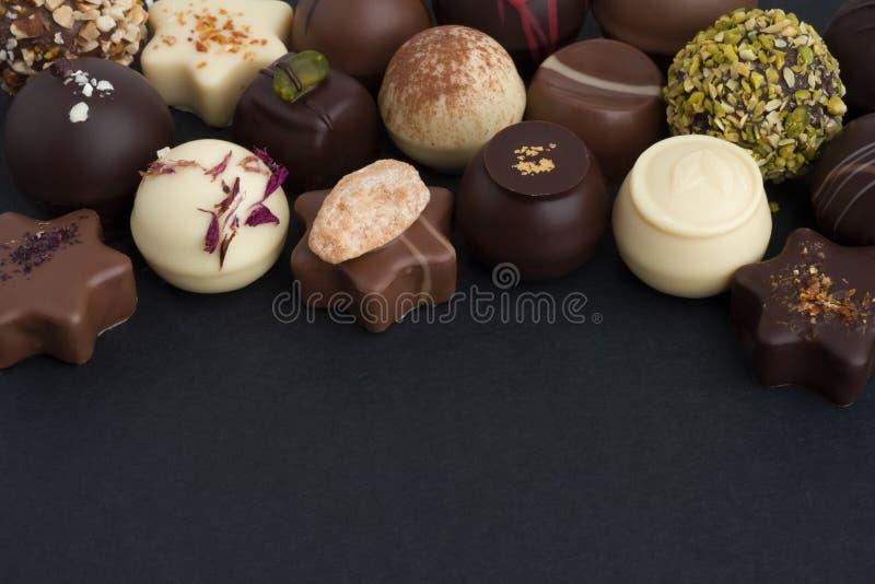 Muitos bombons diferentes do chocolate no fundo escuro com espaço da cópia imagens de stock