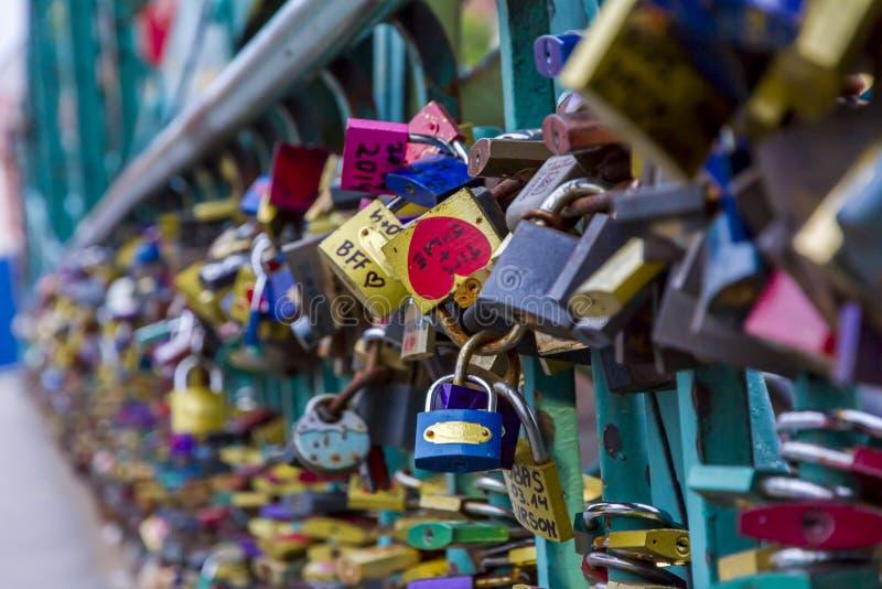 Muitos cadeado coloridos fechados junto em uma ponte imagem de stock