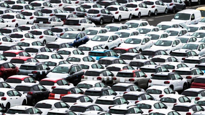 Muitos carros em uma jarda do negócio em um porto na reunião, esperando para obter com os costumes imagem de stock