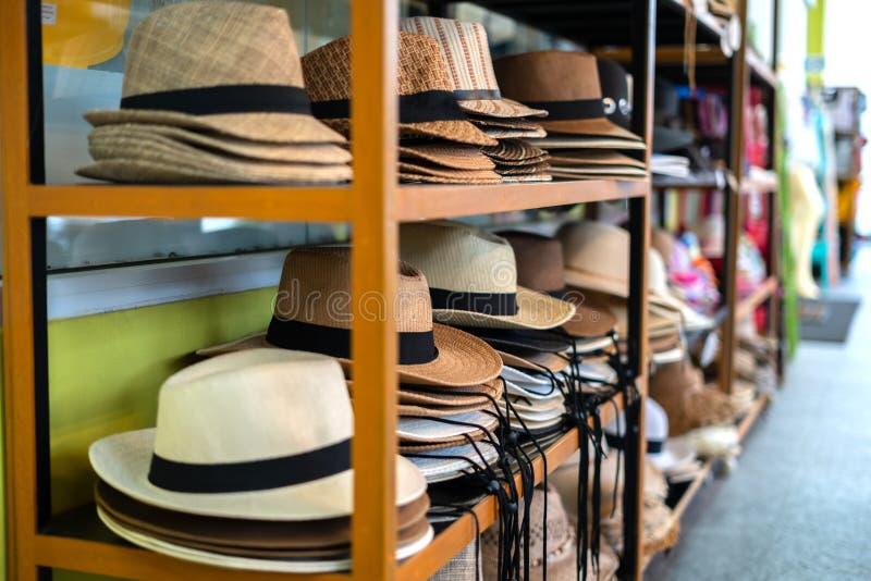 Muitos chapéus do verão e os chapéus de Panamá encontram-se no contador na loja para turistas verão, Tailândia imagens de stock
