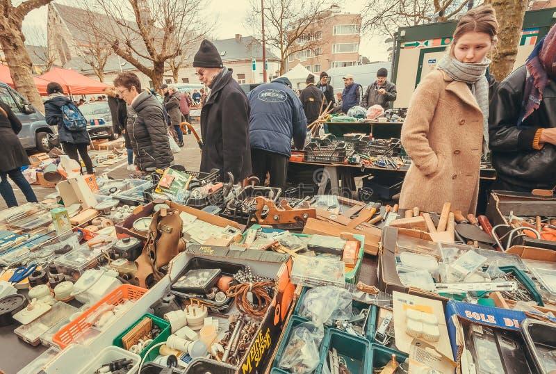 Muitos clientes que olham bens na feira da ladra exterior com utensílios retros, pessoal da segunda mão fotografia de stock royalty free