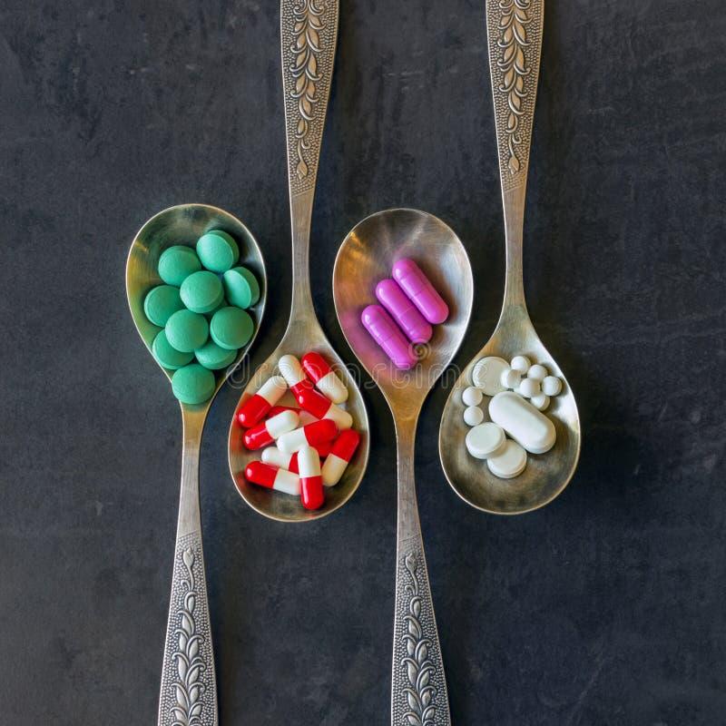 Muitos comprimidos e medicinas coloridos, vitaminas, cápsulas em uma colher em um fundo escuro imagens de stock royalty free