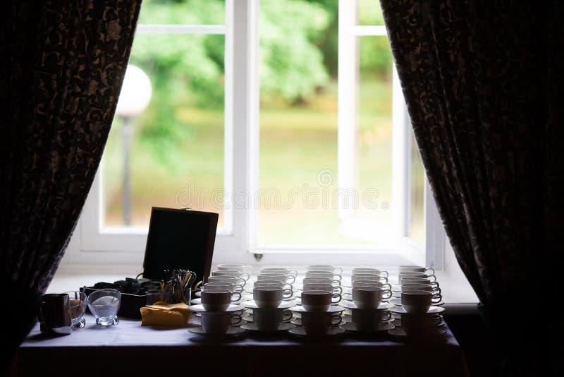 Muitos copos com colheres em uma tabela, para o café ou o chá imagens de stock royalty free