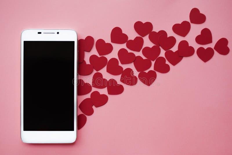 Muitos corações e smartphone Conceito a gostar em redes ou no app social datar Fundo cor-de-rosa foto de stock royalty free