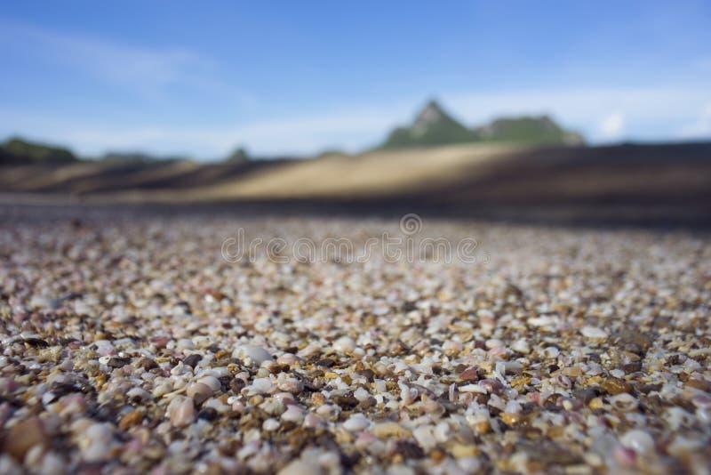 Muitos corais pequenos quebrados, sucata do shell do mar na areia no primeiro plano e céu azul e montanha borrados no fundo imagem de stock royalty free