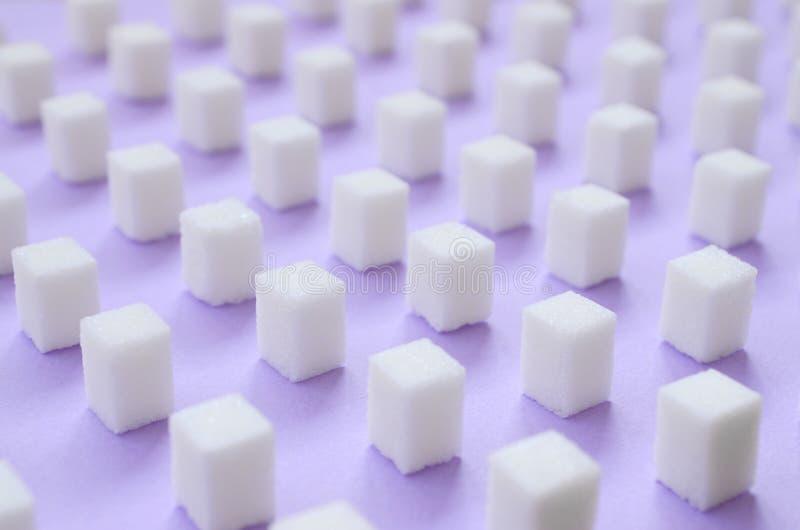 Muitos cubos pequenos do açúcar são alinhados em um fundo violeta foto de stock royalty free