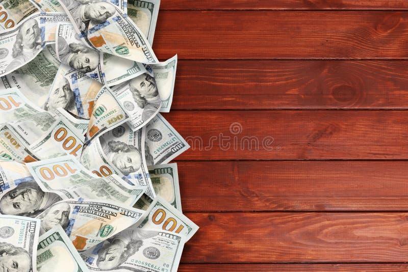 Muitos dólares em um fundo de madeira fotografia de stock