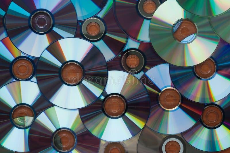 Muitos discos do CD do computador que refletem em uma superfície de madeira, fundo, textura fotografia de stock