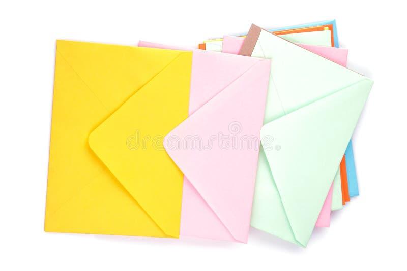 Muitos envelopes postais coloridos em um branco isolaram o fundo Conceito do correio imagens de stock royalty free