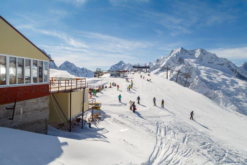 Muitos esquiadores e snowboarders descansam na parte superior da montanha em um dia de inverno ensolarado imagem de stock royalty free