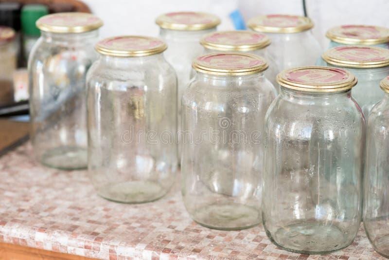 Muitos frascos de vidro que sentam-se na tabela, antes de preservar imagem de stock royalty free