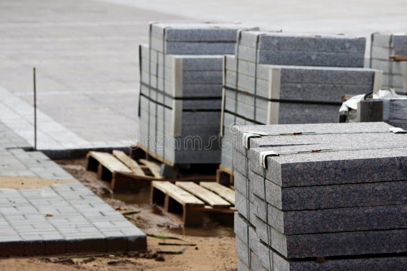 muitos freios para obras em páletes no local que coloca o quadrado de cidade dos pavimentos foto de stock