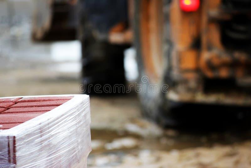 muitos freios para obras em páletes no local que colocam o quadrado de cidade dos pavimentos e em um trator amarelo no fundo fotografia de stock