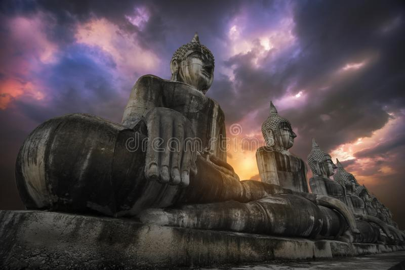 Muitos grandes imagens da Buda e céus alaranjados no distrito de Thung Yai foto de stock