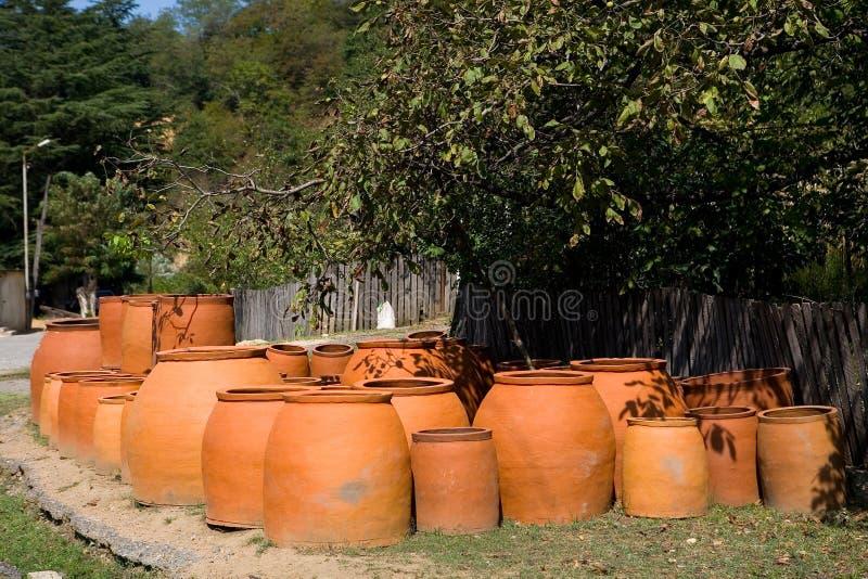 Muitos grandes jarros do produto de cerâmica para o vinho são vendidos perto da estrada imagem de stock