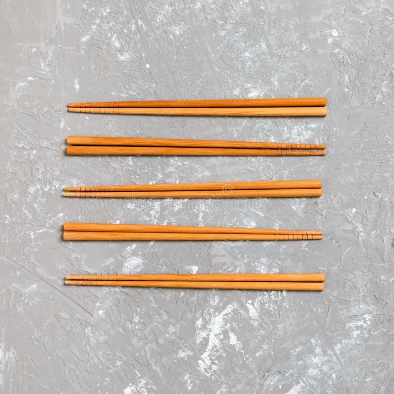 Muitos hashis de bambu no fundo de pedra do cimento preto, vista superior com espaço da cópia muito sushi cola sob a forma do fotografia de stock
